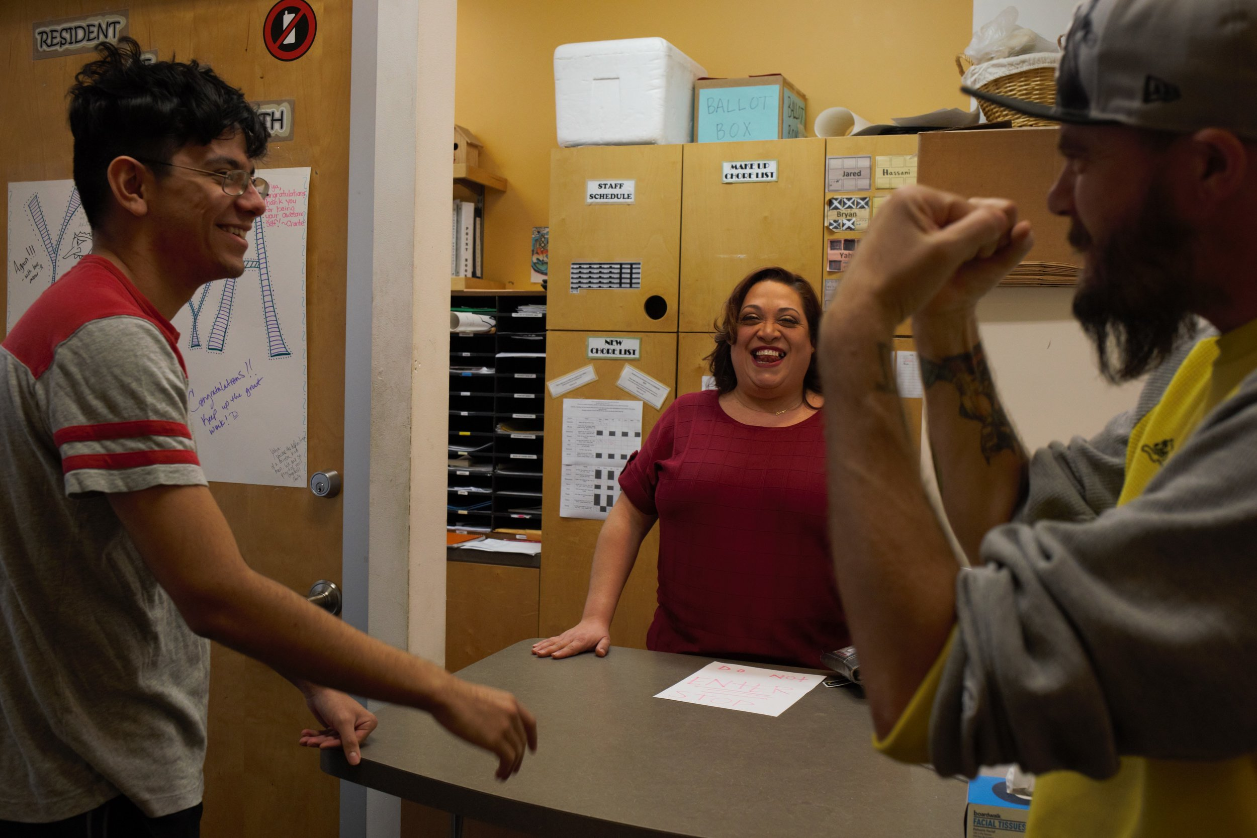 Program manager Beatriz Albelo laughs with residents of a supportive housing program for youth in Chicago.