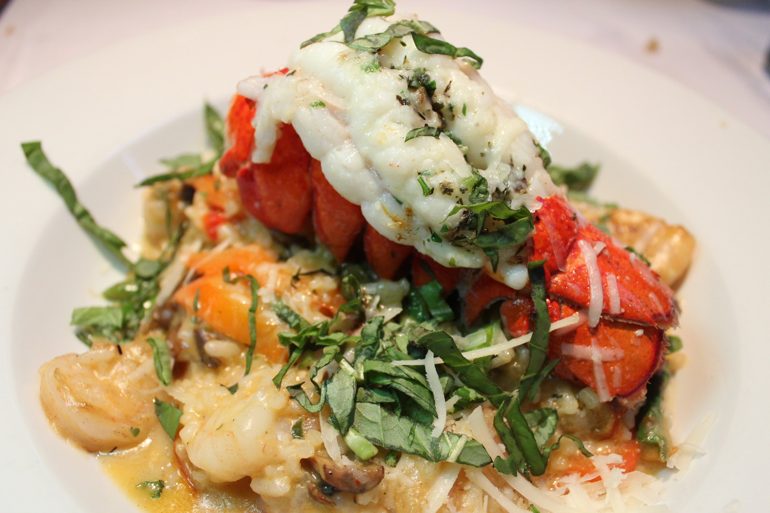 Cold Water Lobster Tail with Shrimp Risotto   Made with mushrooms, roaster red peppers, asparagus, basil and Parmesan topped with a broiled lobster tail.