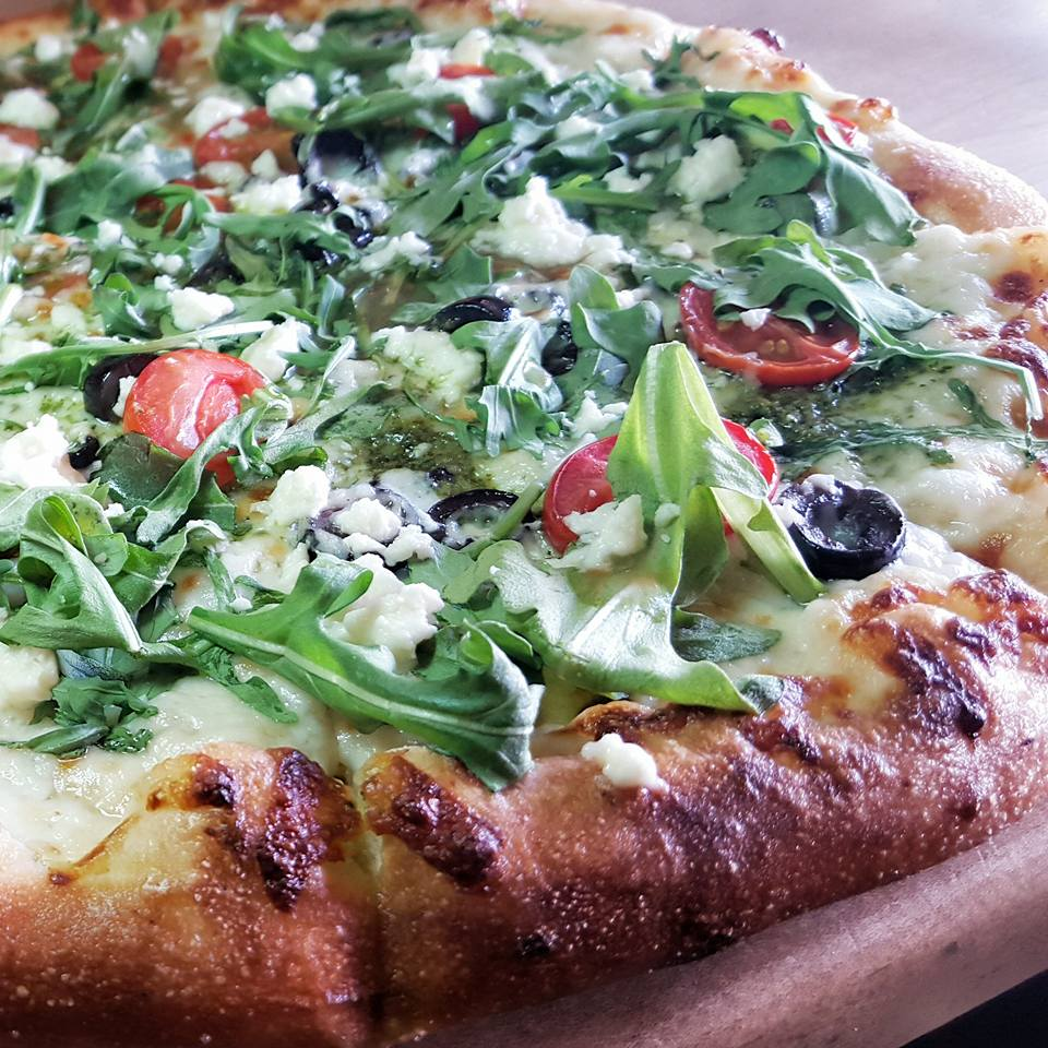 Basil pesto and Wild Arugula Pizza *Flatbread offered at Huntington Beach Location