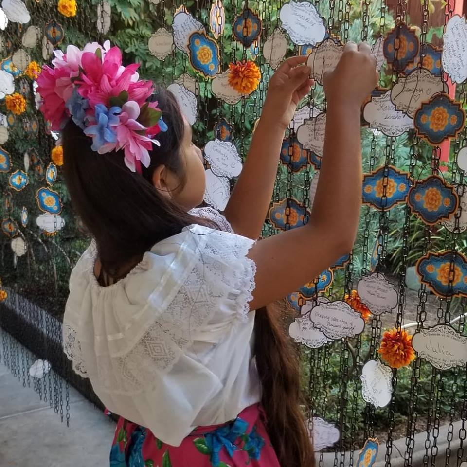 Adding the name of her abuelito to the wall of memories.