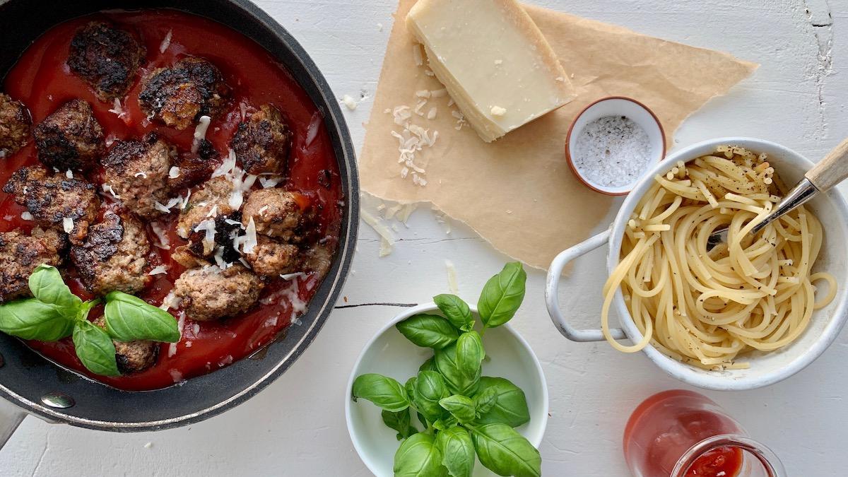 Server spagetti og kjøttboller med revet parmesan og frisk basilikum.