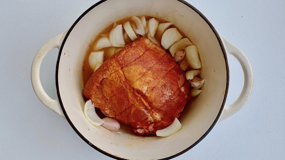 Den krydrede svinenakken får godgjøre seg i en støpejernsgryte sammen med løk, hvitløk og eplejuice i 4-5 timer.