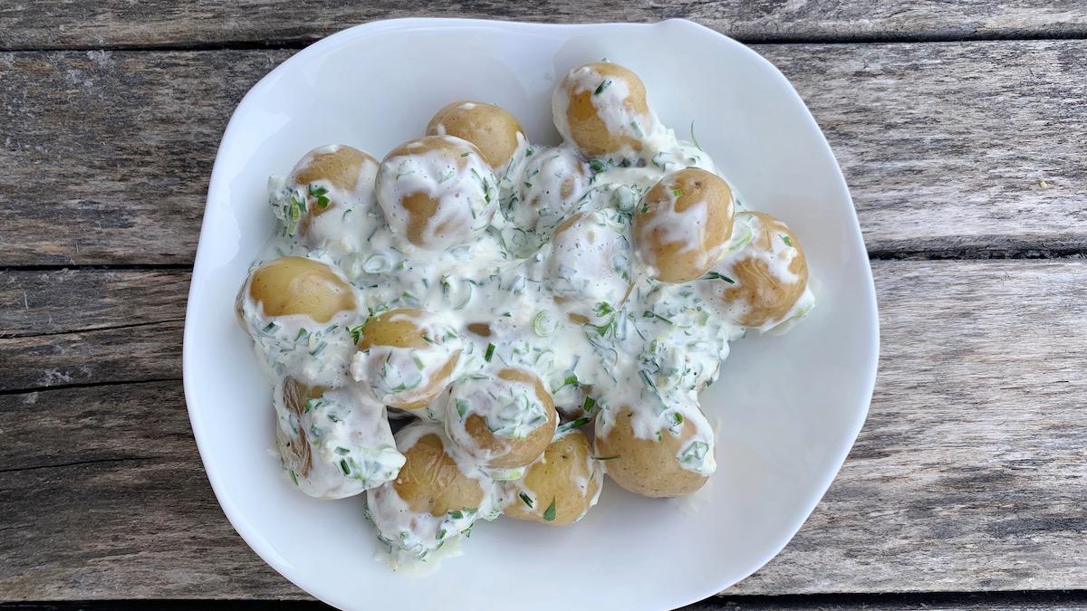En syrlig potetsalat med creme fraiche, urter og sitronskall smaker nydelig til grillmat.