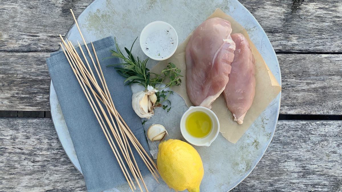 La kyllingen få marinere litt i en blanding av olje, hvitløk, sitron og urter før du deler den i jevne biter og setter den på spyd.
