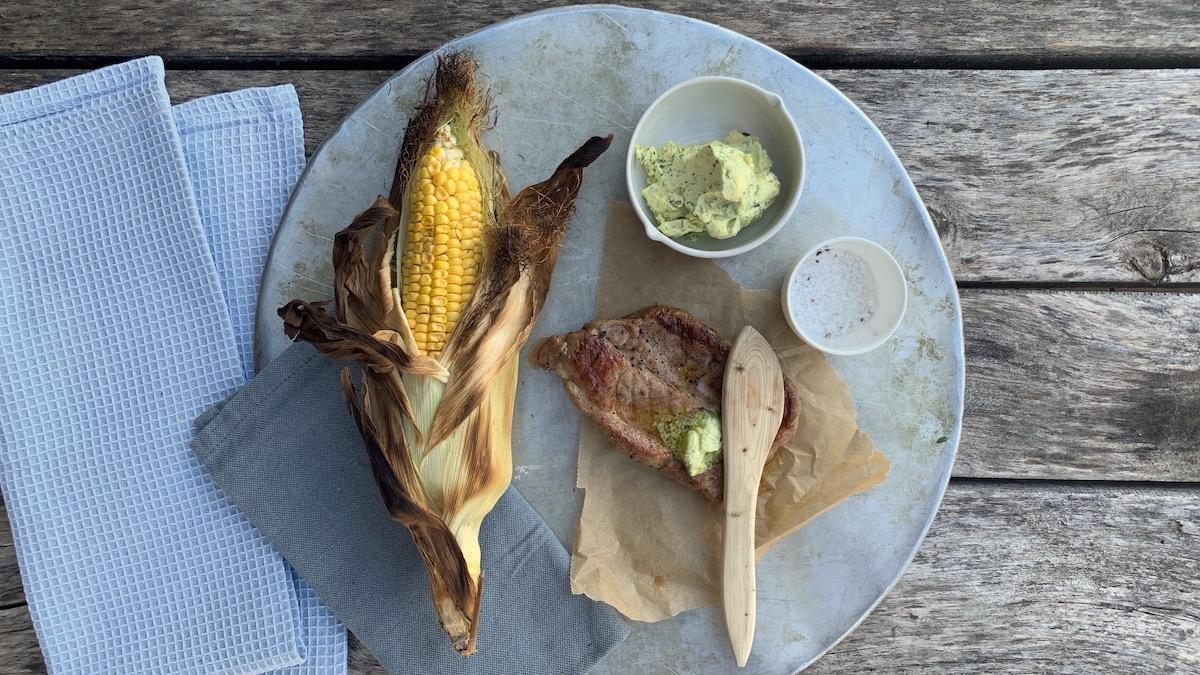 Ferdig grillede nakkekoteletter serveres med grillet mais og en raus skje med urtesmør.