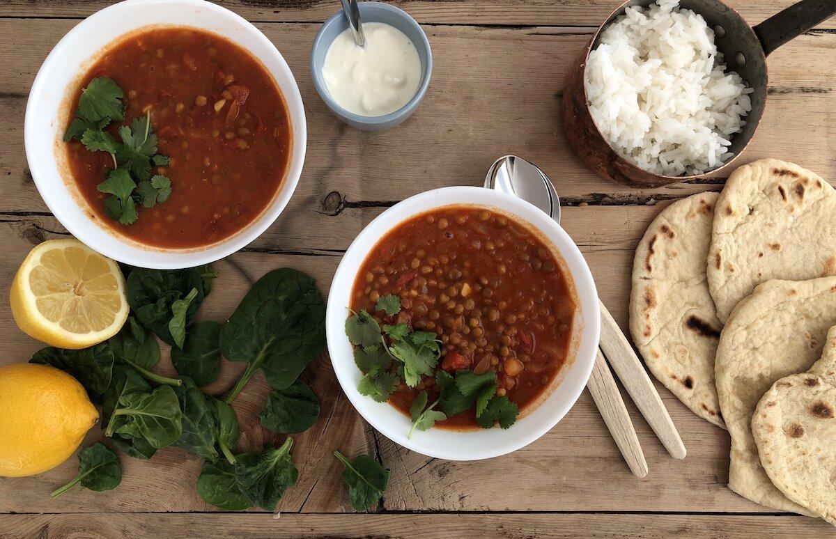 Server indisk linsegryte med ris, rømme og godt brød.