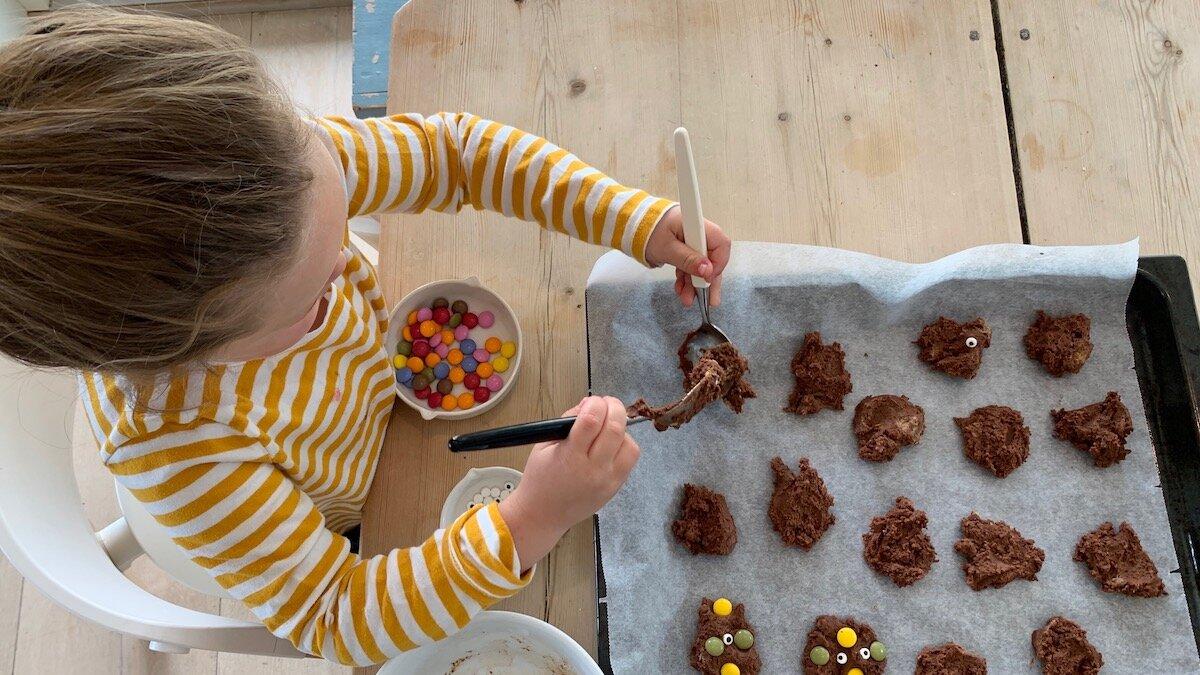 La barna være med å lage monsterkjeks. Hvis de er store nok til forme kjeksene kan de få hele ansvaret, hvis de trenger litt hjelp kan du forme kjeksene først og deretter overlate pyntingen med sjokoladeknapper og øyne til dem.