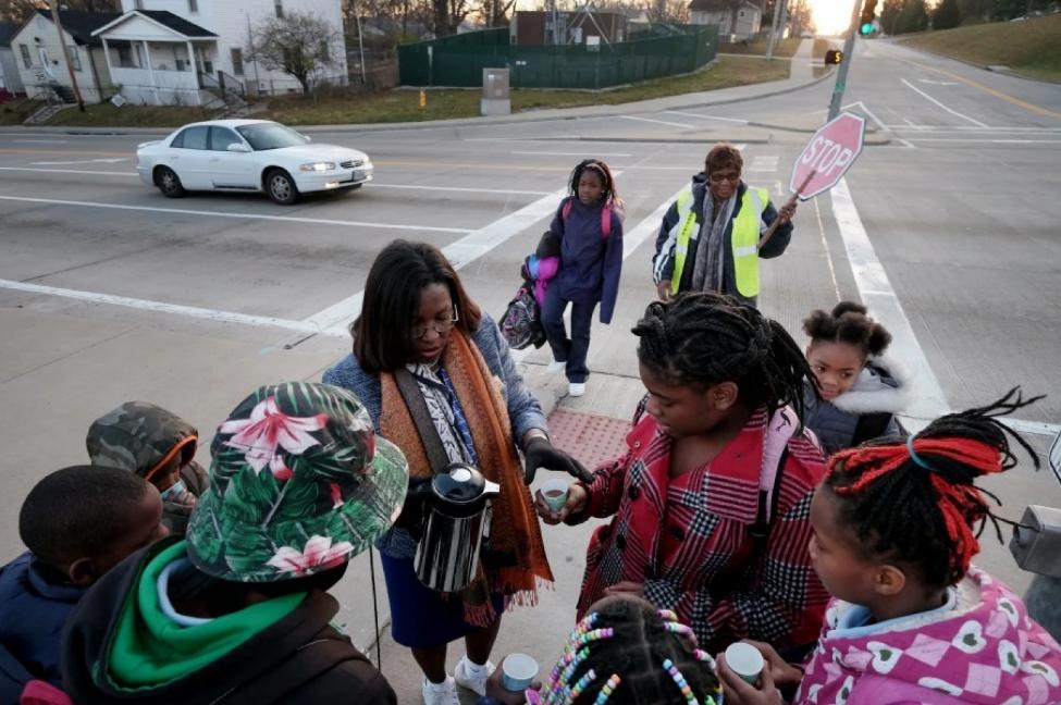 Tiffany Anderson, the superintendent of the 3,000-student Jennings school district, serves hot cocoa to students on their way to school. Anderson led a turnaround in high-poverty Jennings with the aid of wraparound services like a school-based health clinic and food pantry. (Photo by Bonnie Jo Mount/The Washington Post)