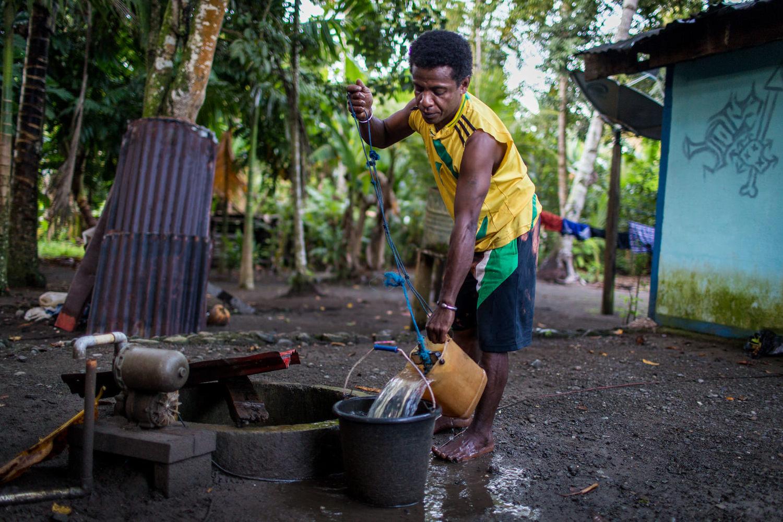 Yosua mengisi ember dengan air dari sumur sehingga adiknya bisa mandi dan bersiap-siap untuk sekolah.