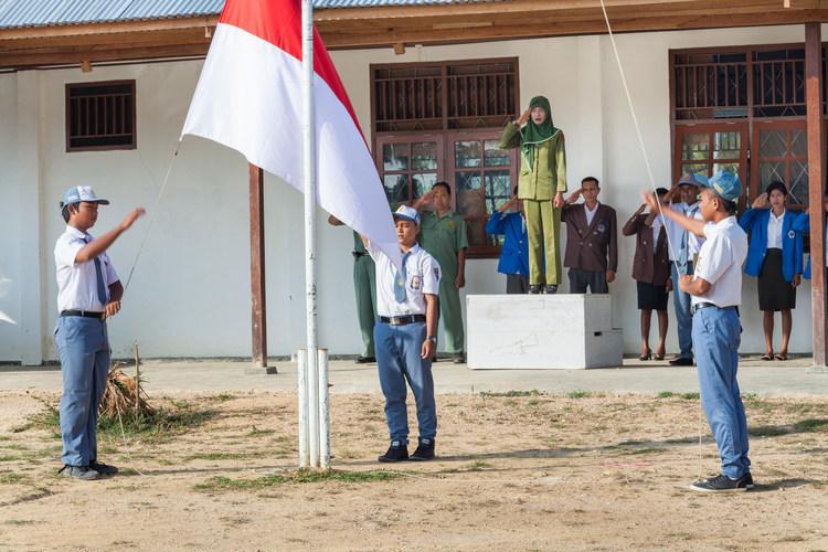Ibu Ratna memberi hormat saat upacara bendera di sekolah.