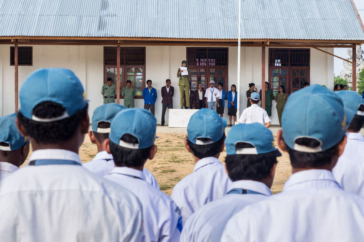 Berdiri di atas podium, Ibu Ratna memimpin jalannya upacara bendera di sekolah.