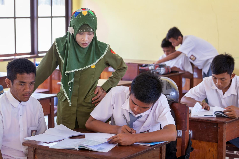 Ibu Ratna mengawasi murid-murid di dalam kelas. Ia sudah berprofesi sebagai guru selama lima tahun dan saat ini ia mengajar lebih dari 120 murid.