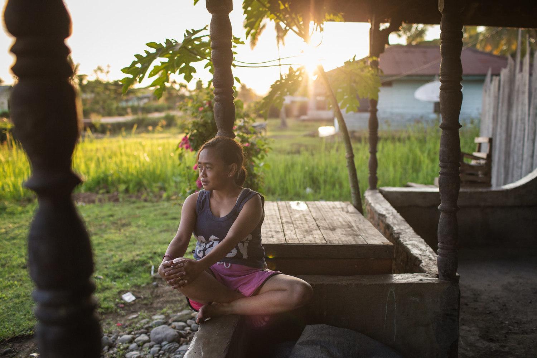 Reni duduk di teras depan menikmati hangatnya sinar matahari sambil melamun dan tenggelam dalam pikirannya sendiri.