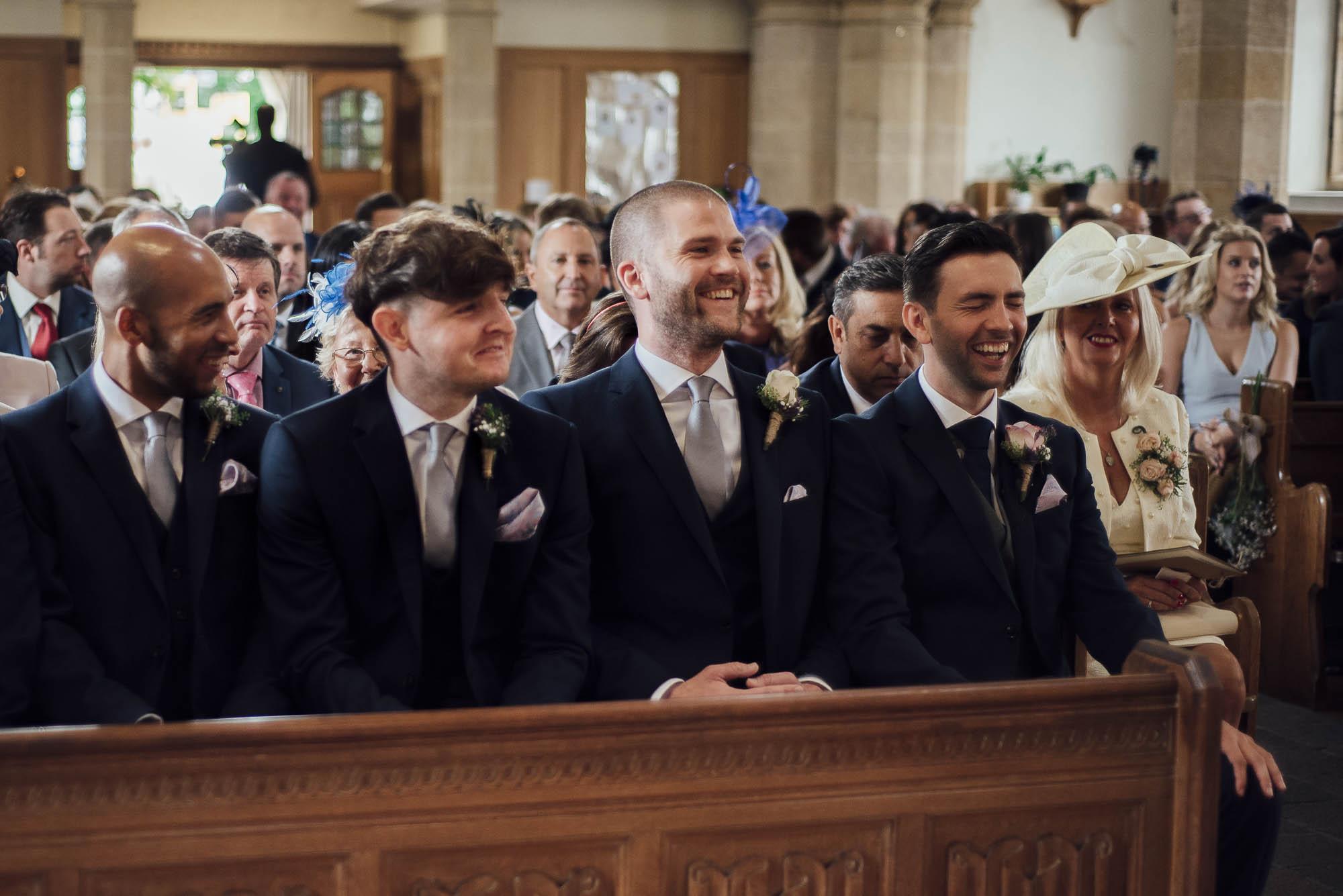 Groom & ushers share a joke at church wedding