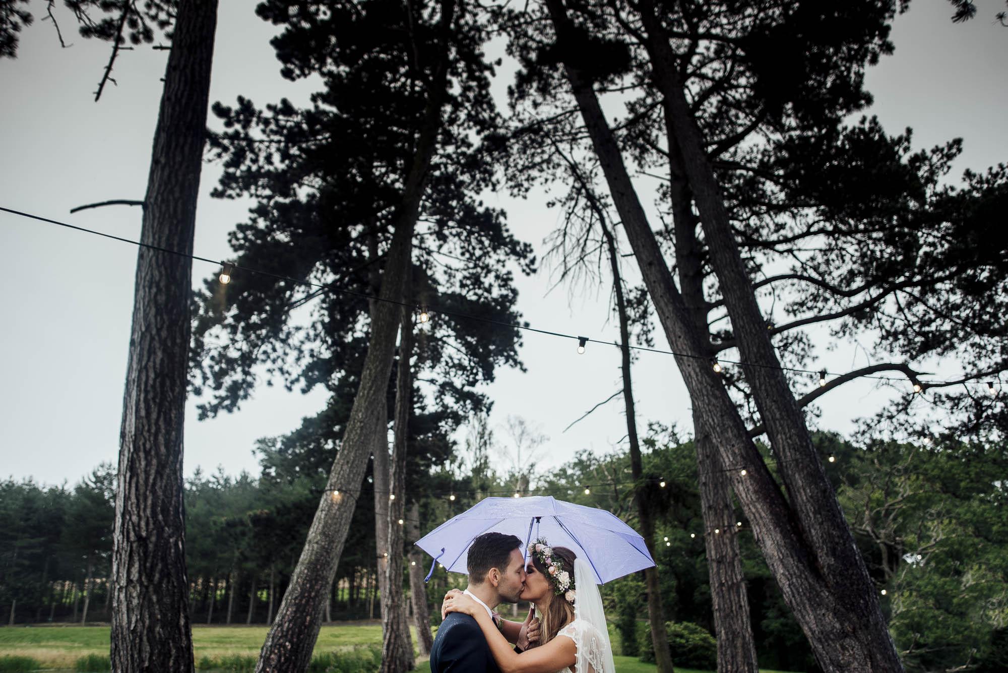 Bride & Groom under an umbrella on a rainy wedding day