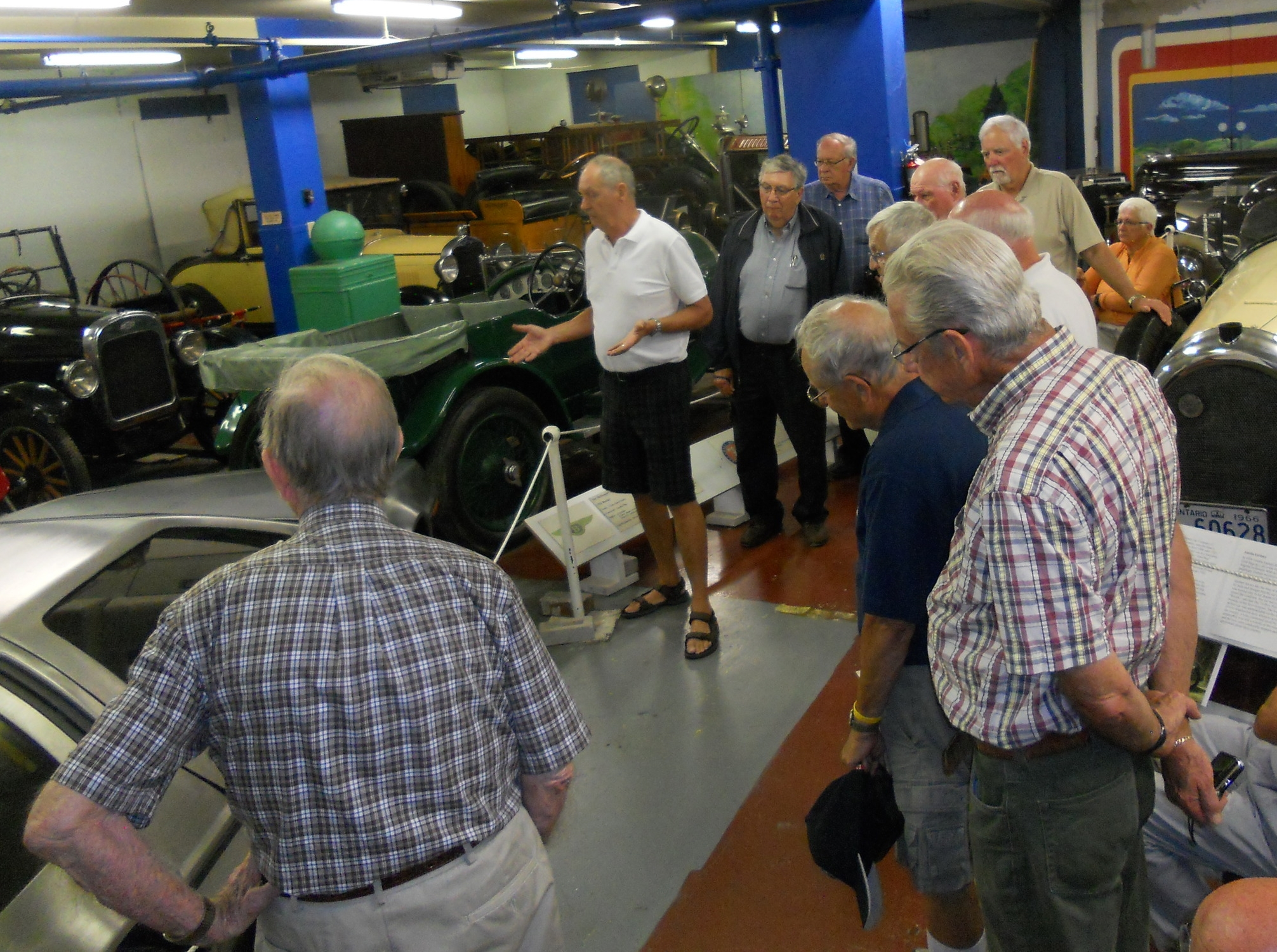 A volunteer tour guide giving a tour of the Canadian Automotive Museum galleries.