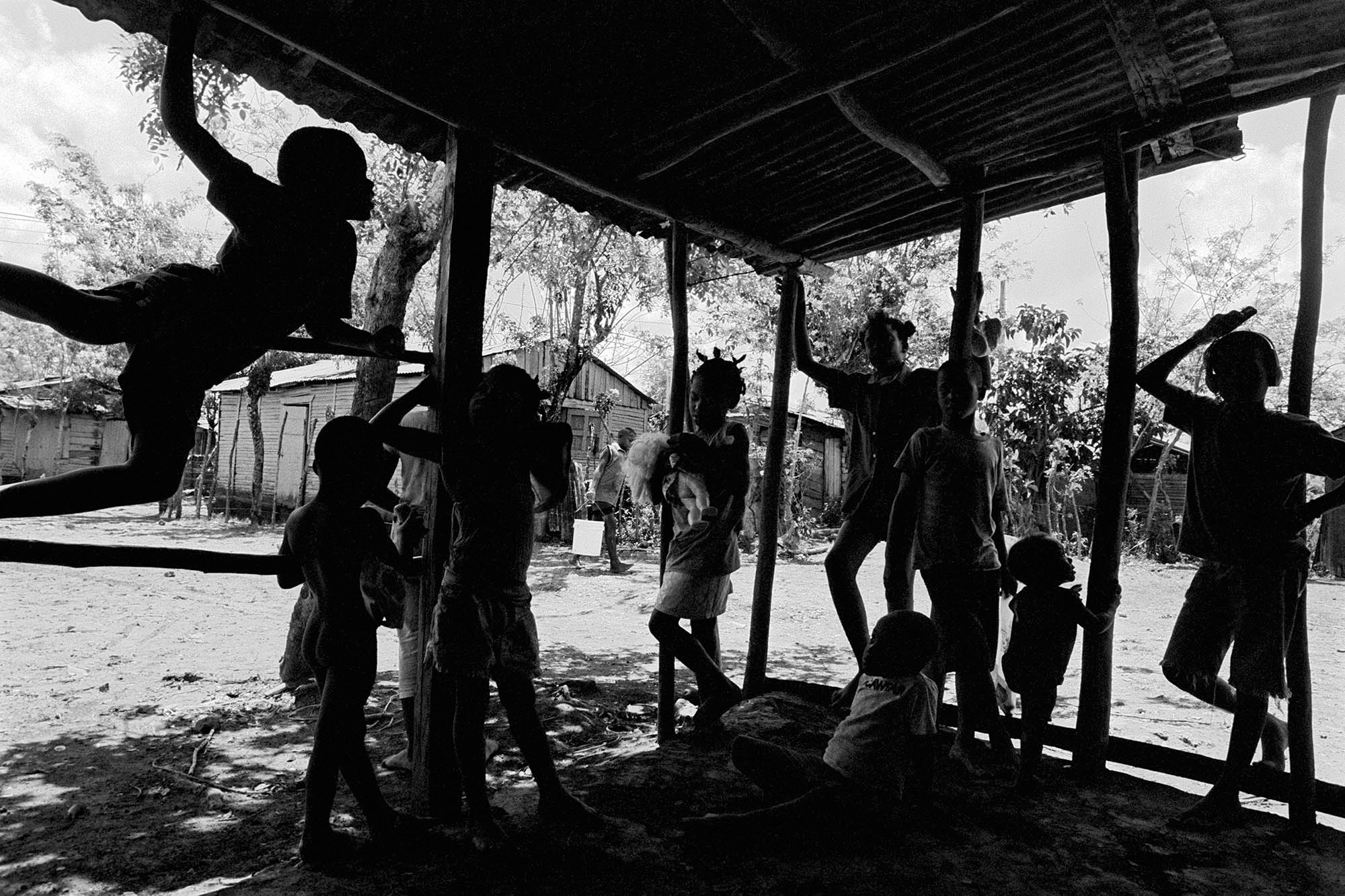 While increasing numbers of people have moved from the bateyes into urban centers like Santo Domingo and Santiago, large numbers of Dominico-Haitians still live in poverty-stricken 'bateyes' on old sugar estates. Children play in a batey in central DR. Most of the children do not possess any documents.