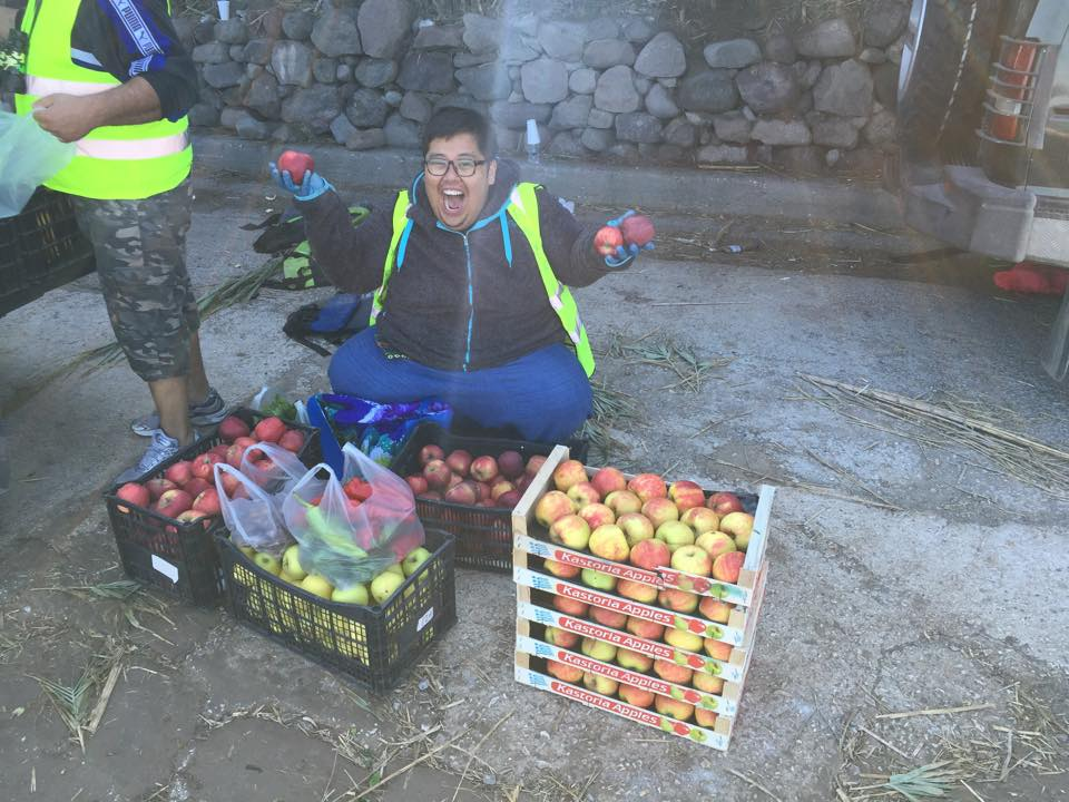 Photo of Rayyan Harries, aka The Volunteer Cook, at Skala Camp, excited about the fruit delivery.