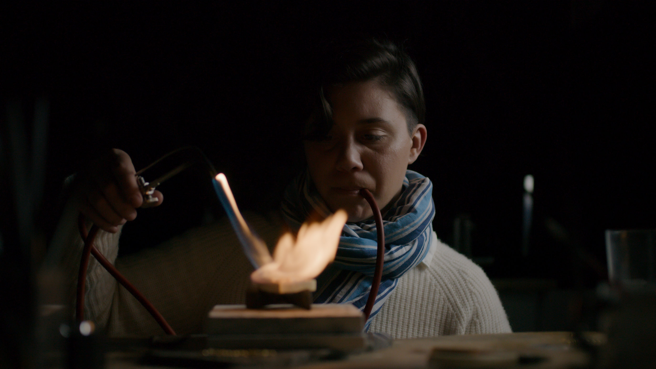 Teetelli shown in her atelier, using an early form of torch called a blowpipe torch in which the user breathes oxygen into the flame, to control the temperature.