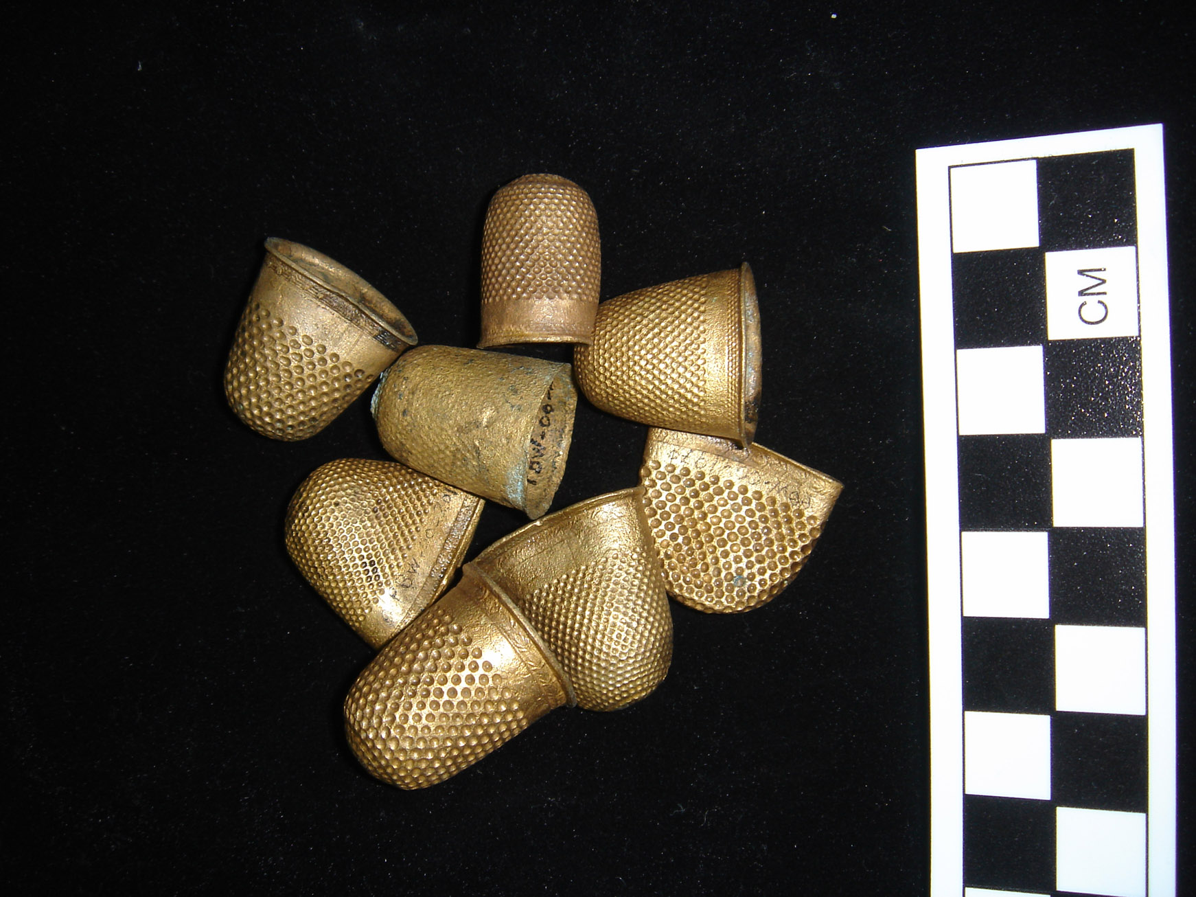 A collection of copper alloy gilt covered thimbles, which were part of the cargo, after ONPCS conservation