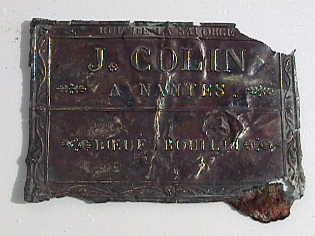 One of the first diagnostic artefacts, a copper alloy label from a tin, confirming that the tin was made from J Colin rue de la Salgorge from Nantes, France