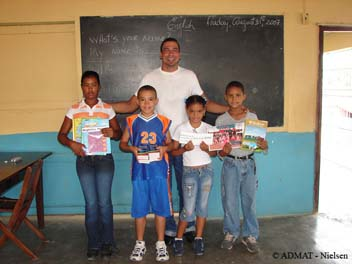 Students holding up the books, dictionaries and money donated by ADMAT and students from the Highbury Primary School in Salisbury, England.