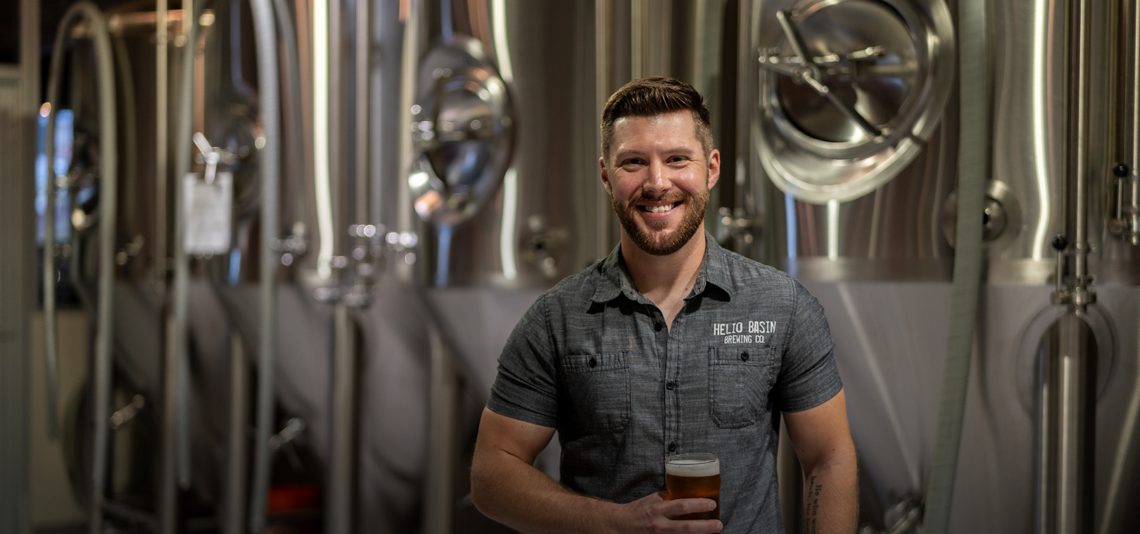 """Dustin Hazer, Owner & brewmaster   With a background in Pharmaceutical Science, Dustin left the research world to attend the Siebel Institute's World Brewing Academy in Chicago, IL several years ago. After completing the coursework there, he went on to start his brewing career at Ellicottville Brewing Company in Western New York, getting to apply all aspects of his learned technical brewing skills in the 1,000 bbl/year setup.  After two years in Ellicottville, Dustin left for an opportunity to brew at Arizona's largest craft brewery, Four Peaks Brewing Company in Tempe. Dustin was there while the operation expanded from around 18,000 bbls per year to close to 40,000 as both a brewpub and distribution brewery. After about three years in the Valley, a large opportunity arose. A friendly phone call from Southern Tier founder Phin DeMink, sharing plans of an upcoming brewhaus expansion as well as other new projects, led Dustin back to Western New York. He was the Brewmaster with Southern Tier Brewing Company for almost four years where he was in charge of all brewing operations, commissioning the new 110 bbl Steinecker brewhaus, along with new 660 bbl and 880 bbl fermenters, cellar and yeast automation and a new state of the art centrifuge. During that time, they grew from around 40,000 bbls per year to producing over 100,000 bbls per year, becoming one of the top 35 breweries in the country.  Now back in the Valley of the sun, he is excited to get Helio Basin Brewing Company established for all to enjoy.  """"I feel very fortunate to have been a part of three great breweries throughout my career and to have learned and worked alongside some of the best people you could hope to meet. The camaraderie of the industry has really shown through, as everyone has been very supportive with this endeavor and we are looking forward to making great beer, great food and establishing a sense of community here at Helio Basin Brewing."""" – Dustin Hazer"""