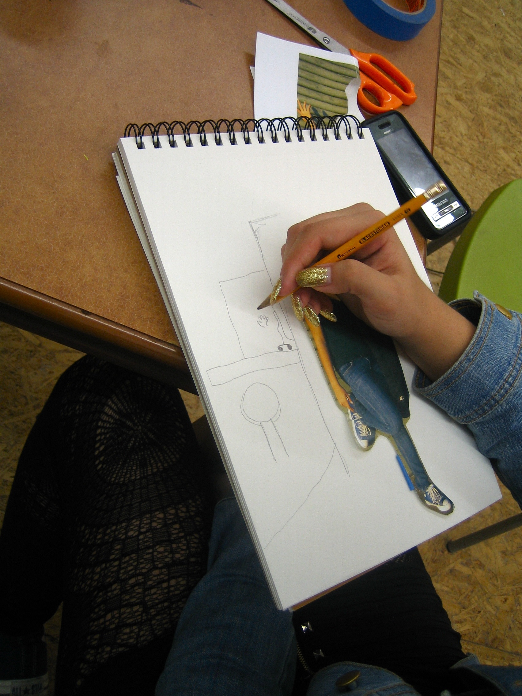 Chey working on her final sketch, depicting a prison visiting room.