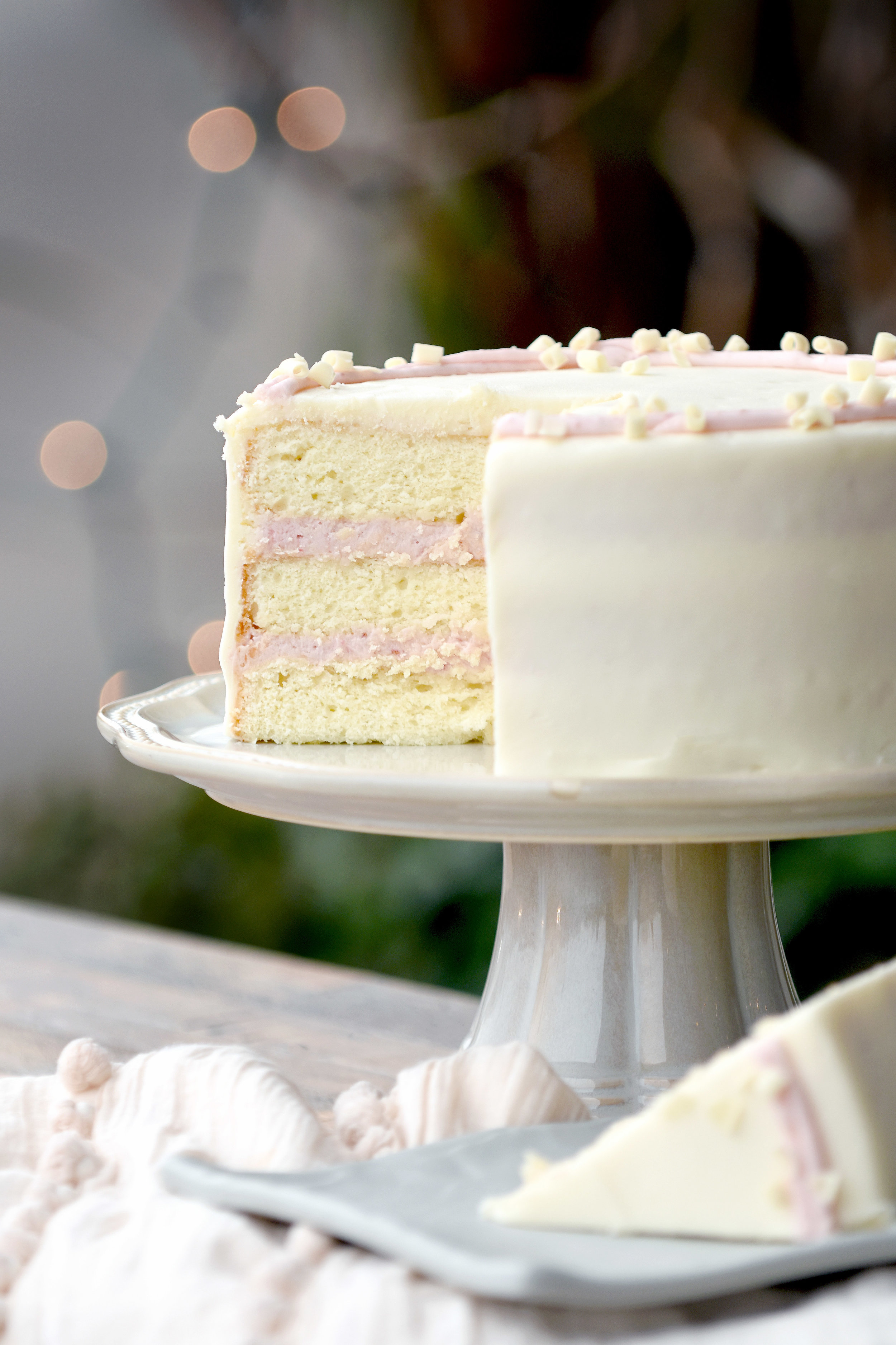 Raspberry Lady Cake   35 half / 62 whole  We just gave this cake a fresh update for spring! It's the  prettiest  cake on the bar! Rich cream cheese layer cake slathered with raspberry cream cheese icing between the layers that is made with Greensboro's own  Jammin' George  freshly-made raspberry jam. Iced on the outside with our classic cream cheese icing and trimmed with a delicate raspberry cream cheese border and white chocolate curls.
