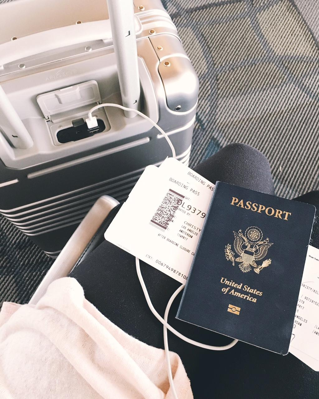 Pink sweater black leggings boarding pass US Passport champagne Arlo Skye carry on luggage