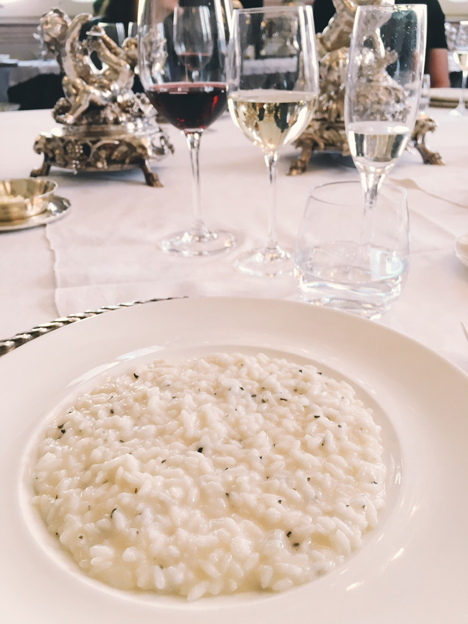 Rosemary risotto and red and white wine at table in Villa Sola Cabiati