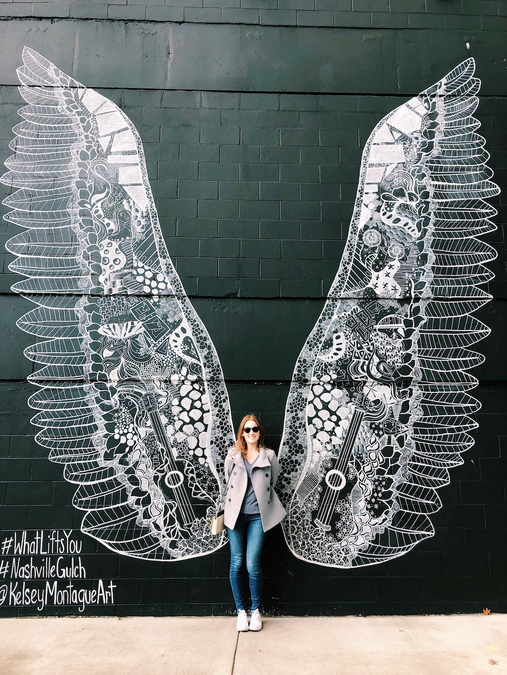 Redhead girl in front of large black white wings