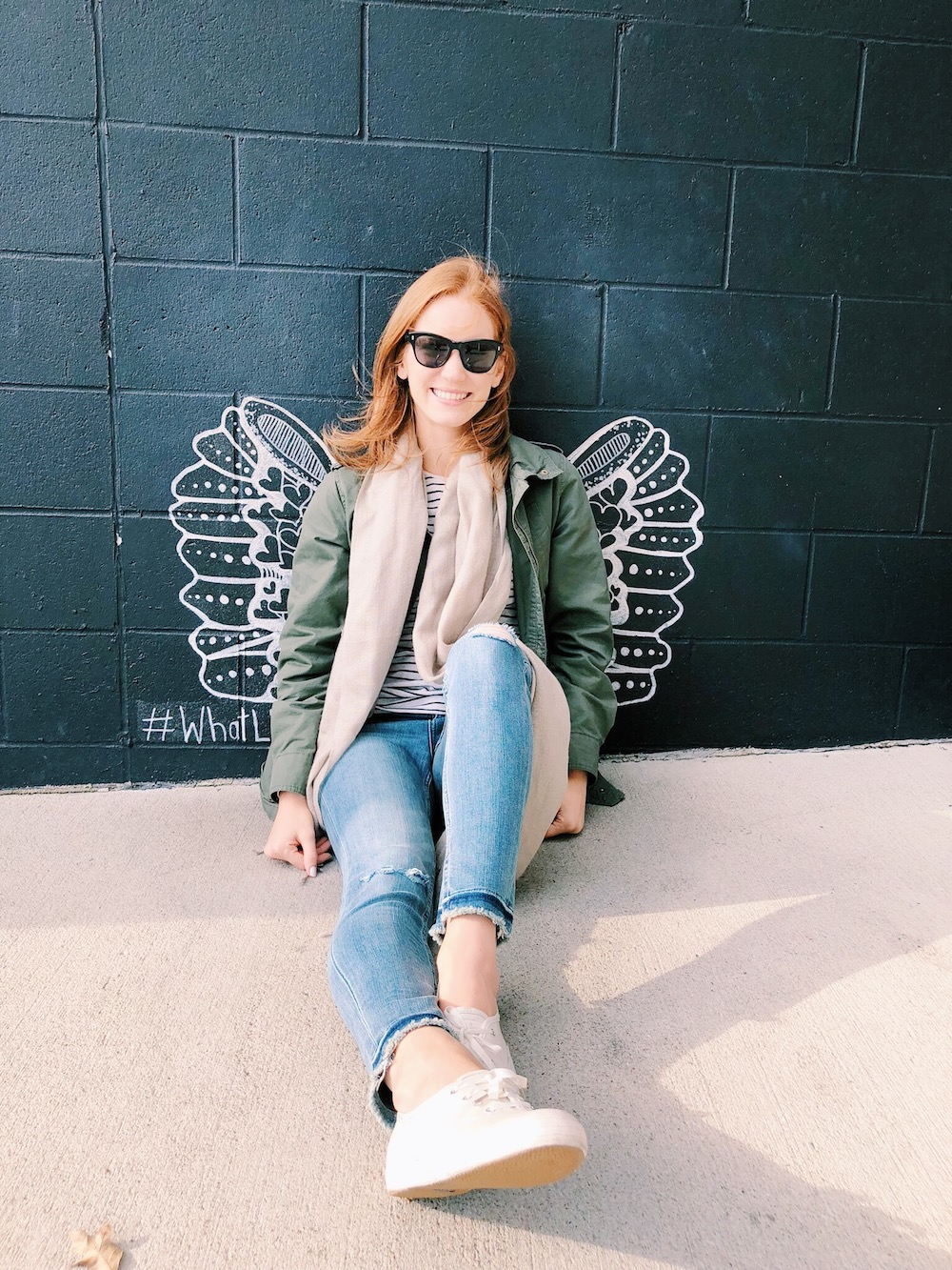 Girl sitting by white wing mural