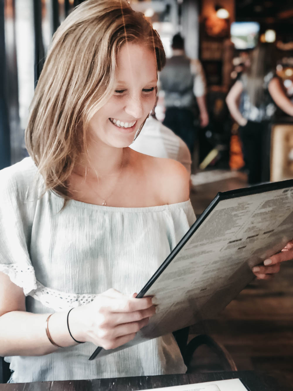 Smiling woman looking at Ft. Lauderdale menu