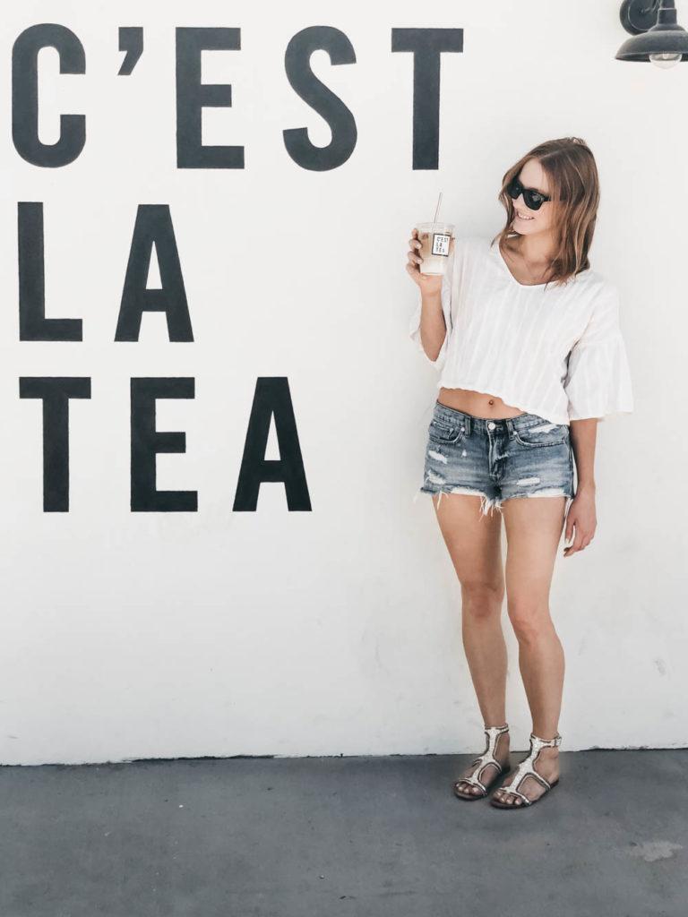 Red head woman with C'est La Tea mural