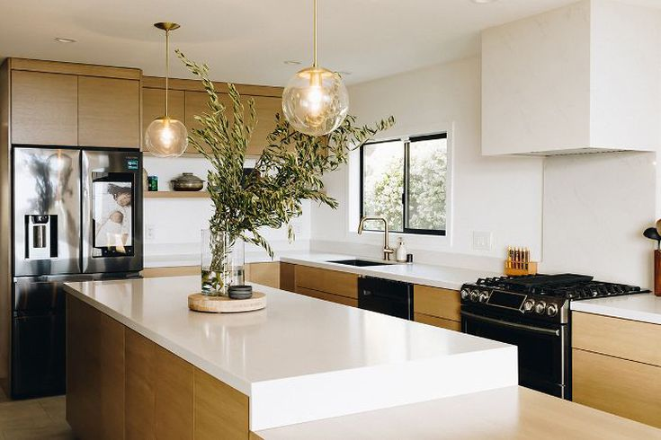 We love the clean and minimal kitchen with bright white countertops, light wood cabinets, and brass fixtures. Photo: Karla Ticas; Design: Erick Garcia of Maison Trouvaille