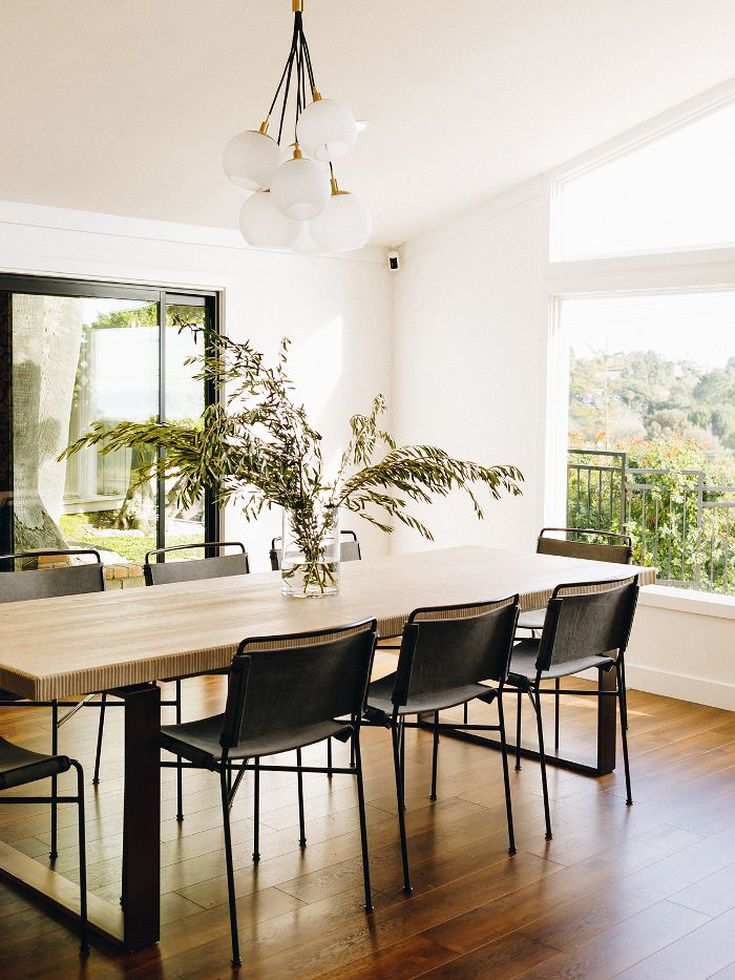 More natural light floods into the chic dining room with a sleek table and modern chairs perfect for entertaining. Photo: Karla Ticas; Design: Erick Garcia of Maison Trouvaille