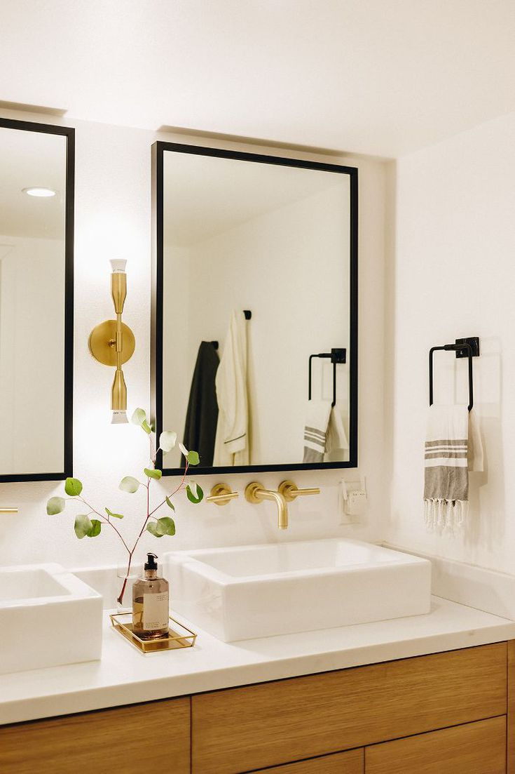 The zen nature of the space continues into the couple's master bathroom with white & black contrast, wood details & brass hardware. Photo: Karla Ticas; Design: Erick Garcia of Maison Trouvaille