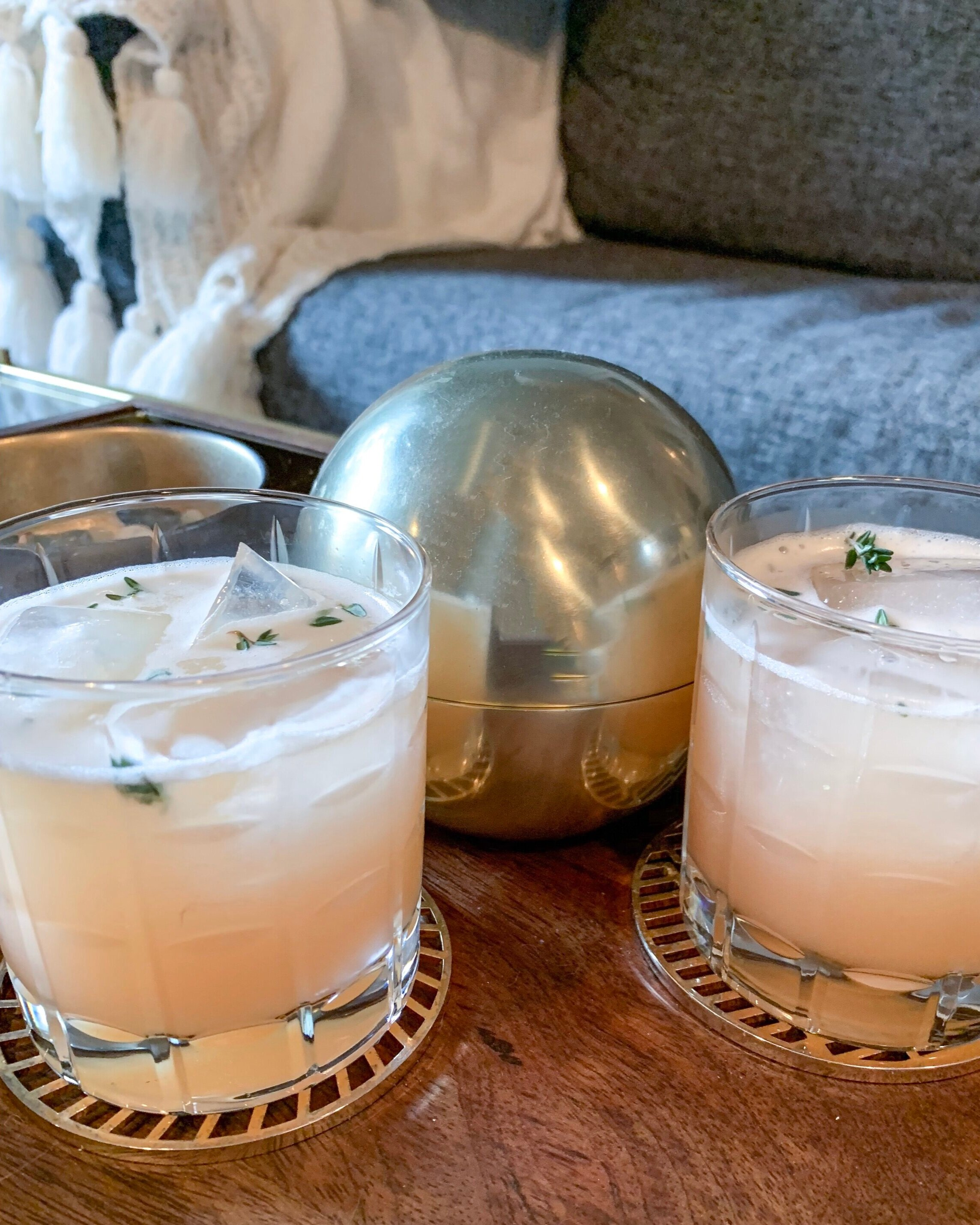 Two paloma cocktails on wood and gold tray