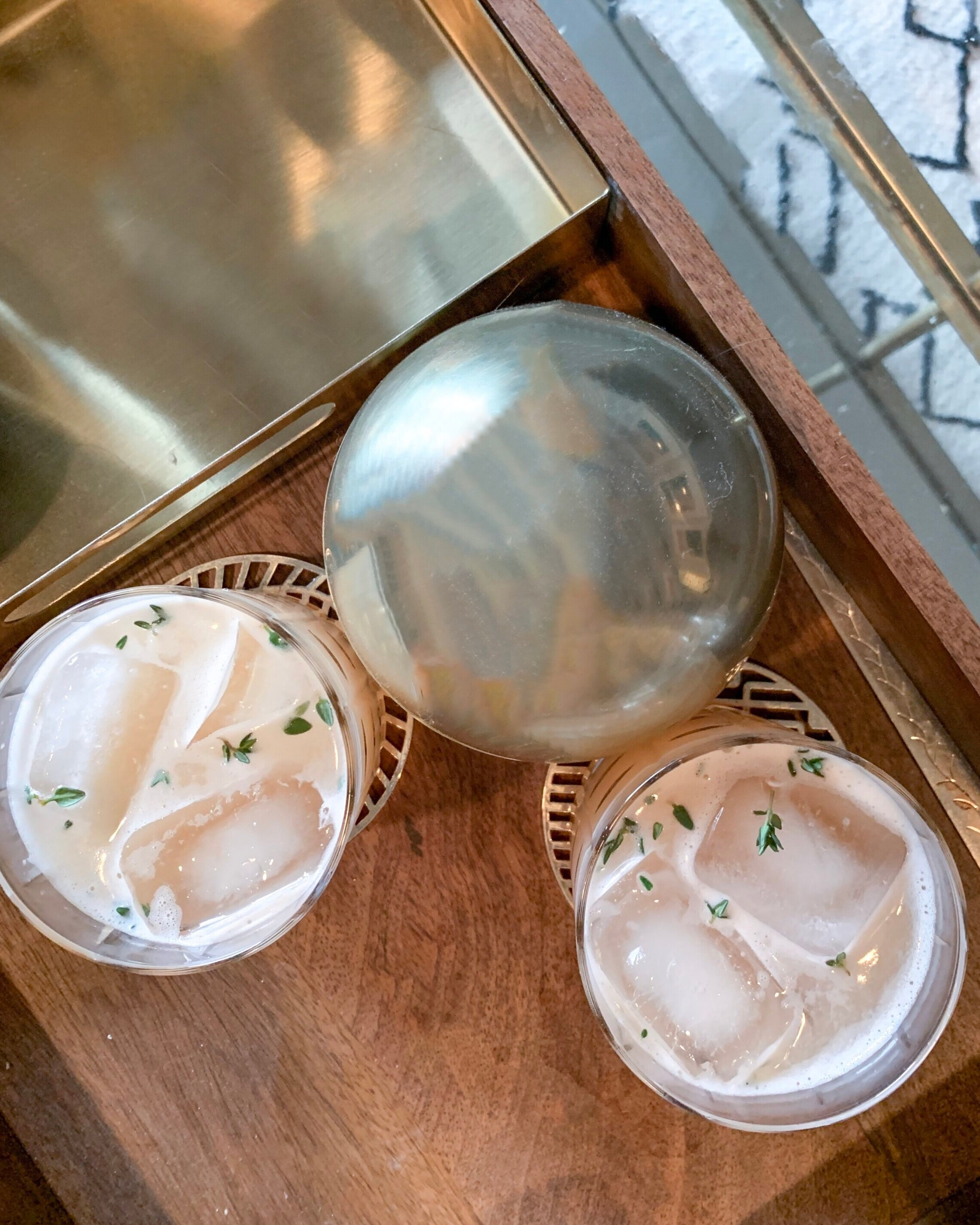 Perfect paloma cocktail with fresh thyme on gold and wooden tray