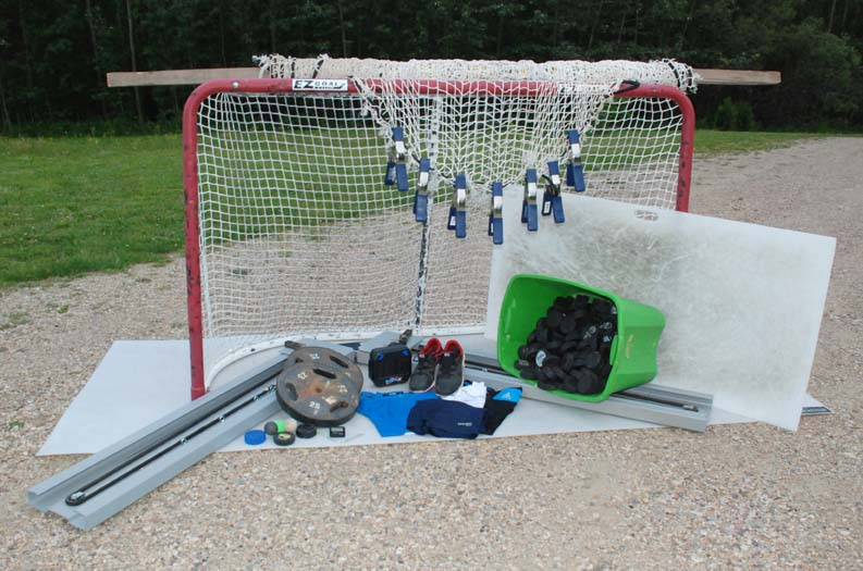 Except for the sports netting hanging over the top of the goal, which I replaced with the goal itself, all the items pictured here see regular service in the course of my training exploits. The grey L-shaped device is the Powerskater skating machine. In the foreground in front of the barbell plates are various practice pucks and balls, my trusty gym timer and two tiny badges I earned at a powerskating course.
