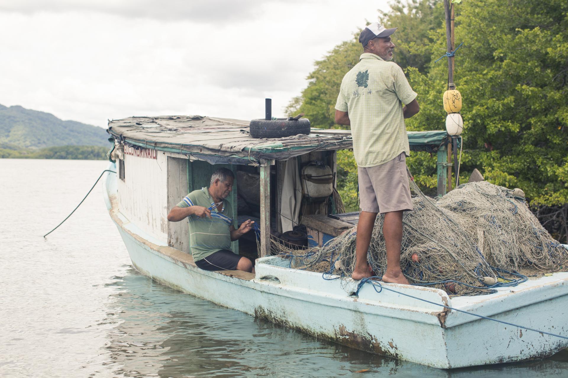 Pescadores en Puerto Níspero arreglan las mallas para la pesca artesanal.