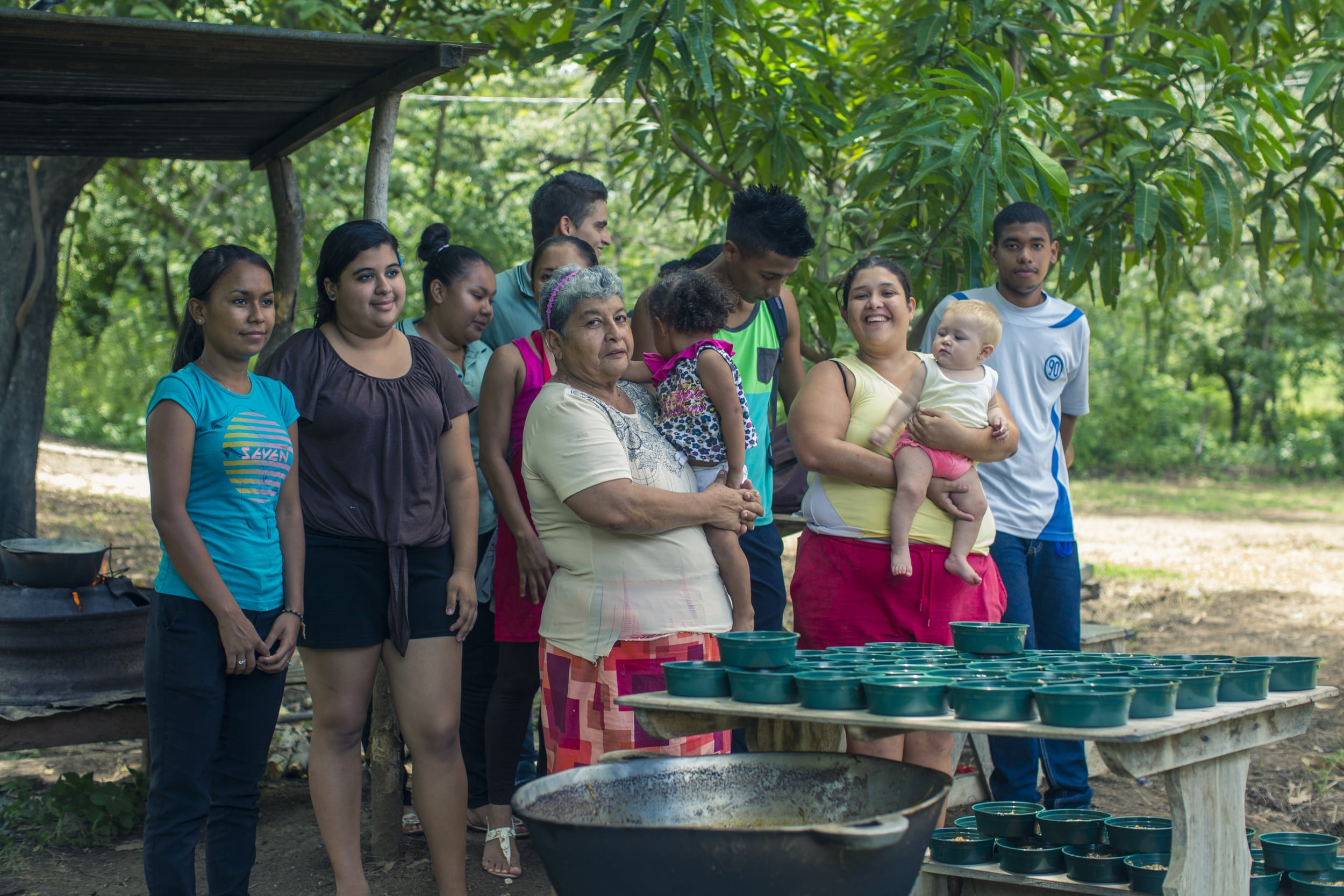 Grupo comunal preparan comida para vender y recaudar fondos para actividades escolares.