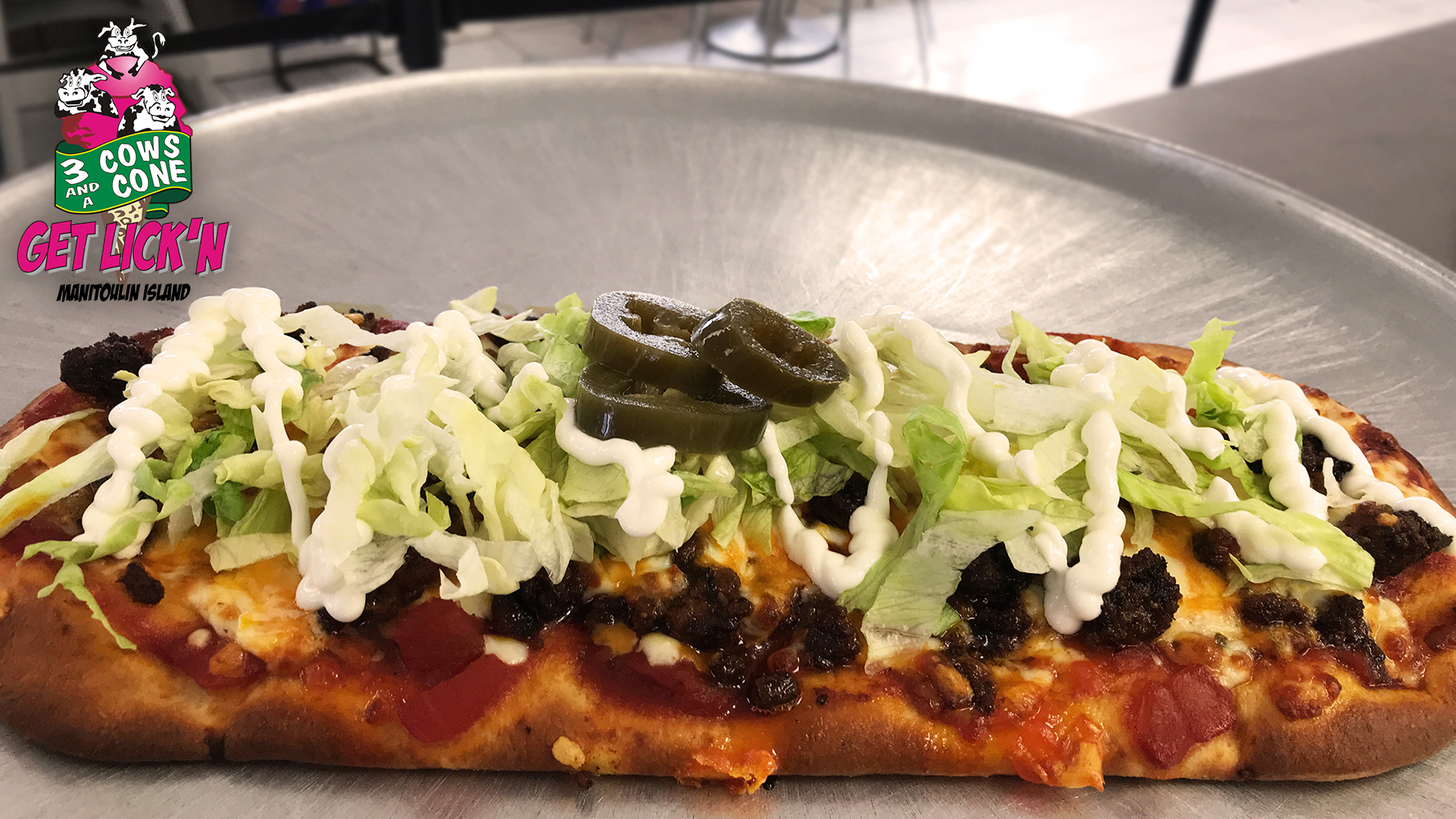 3 Cows and a Cone Taco flatbread.  Made with a salsa base, and topped with seasoned hamburger, lettuce, jalapeños, sour cream, cheddar and mozzarella