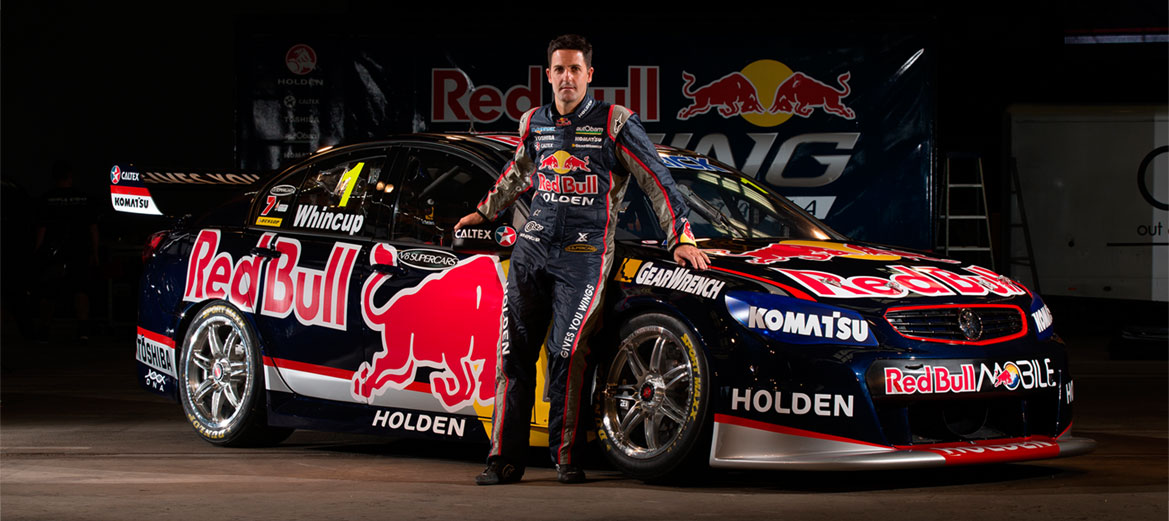 V8 Supercars champion driver Jamie Whincup stands besides the Triple Eight vehicle.