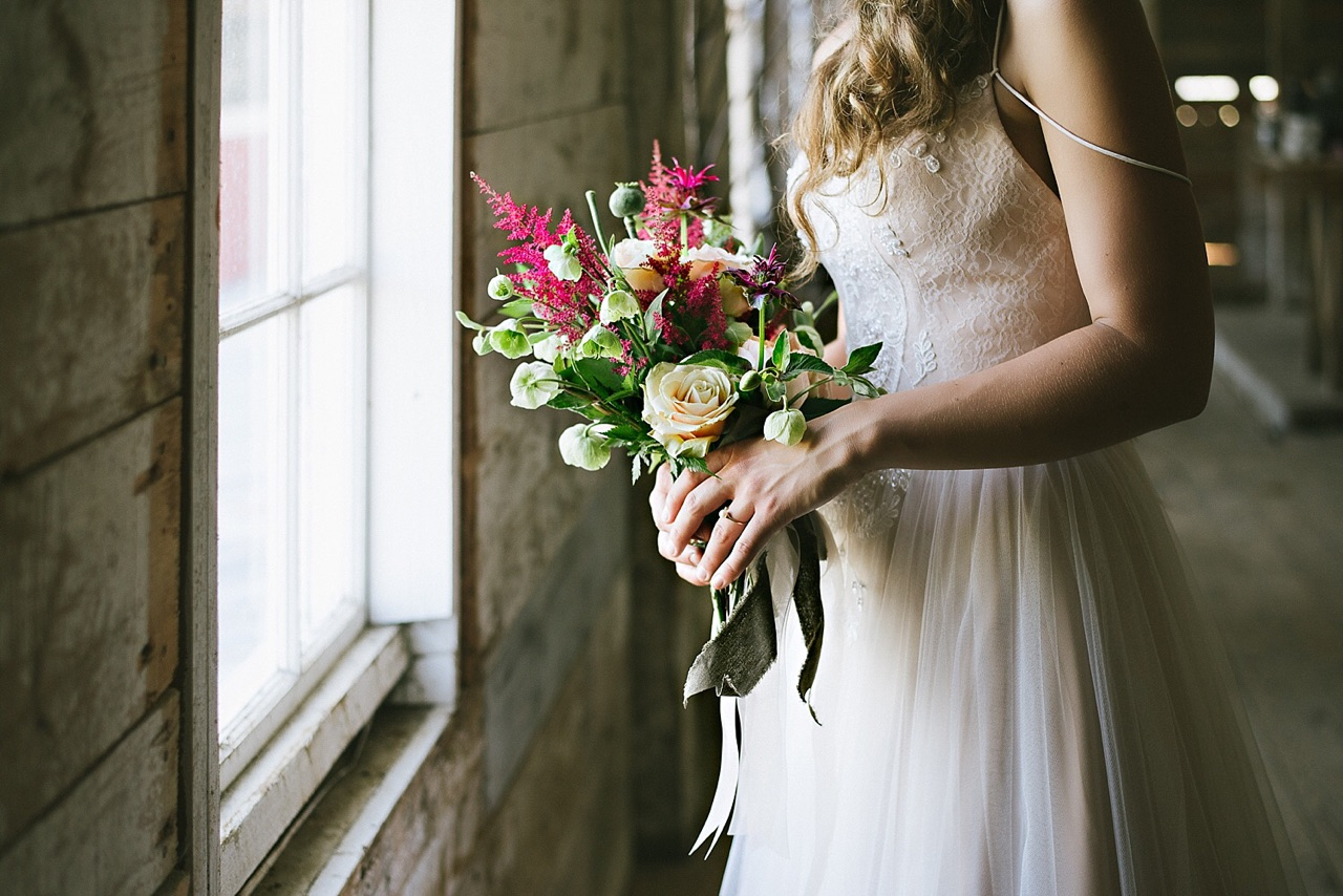 bride holding red and green bouquet in barn