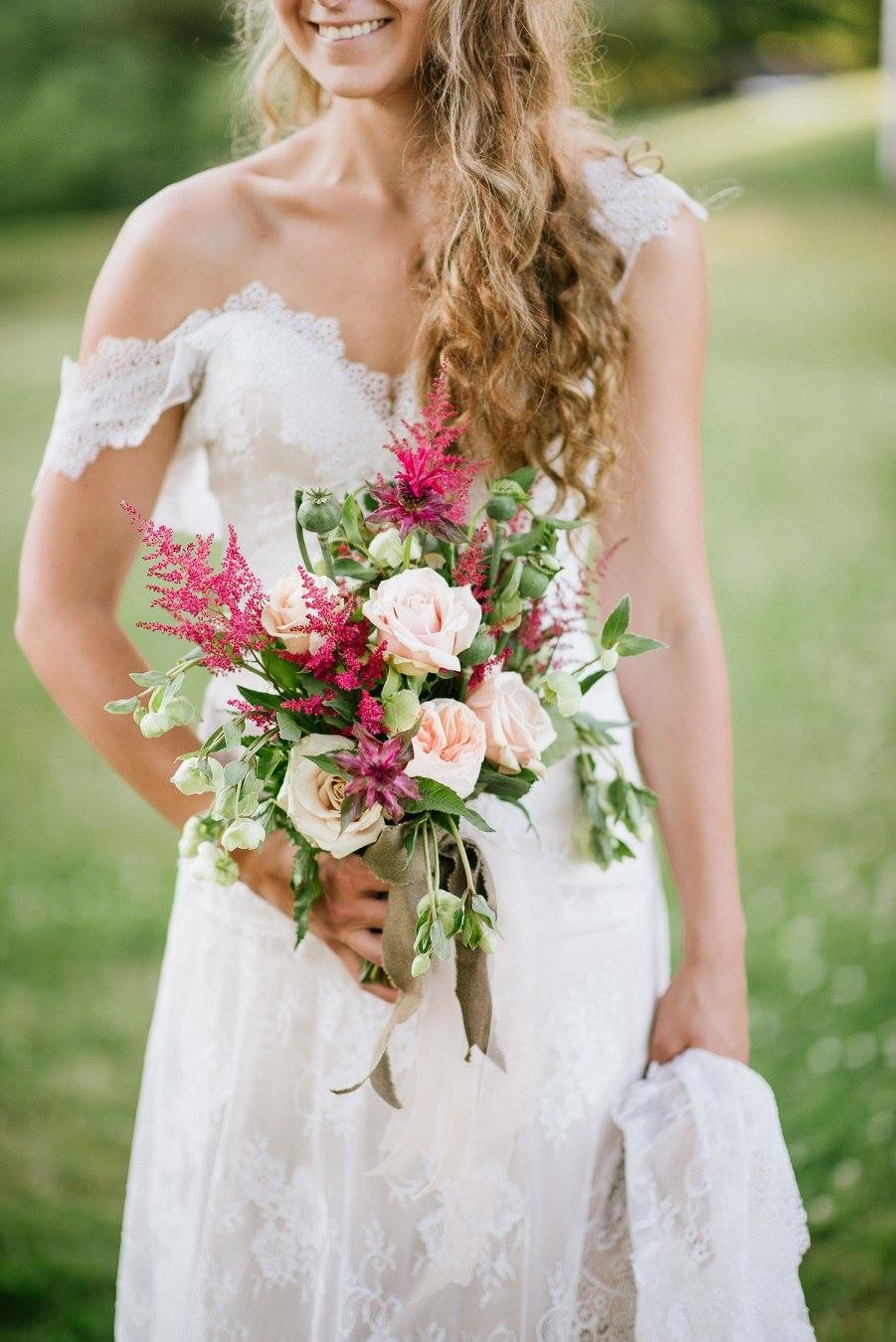 laughing bride with red and pink leafy bouquet