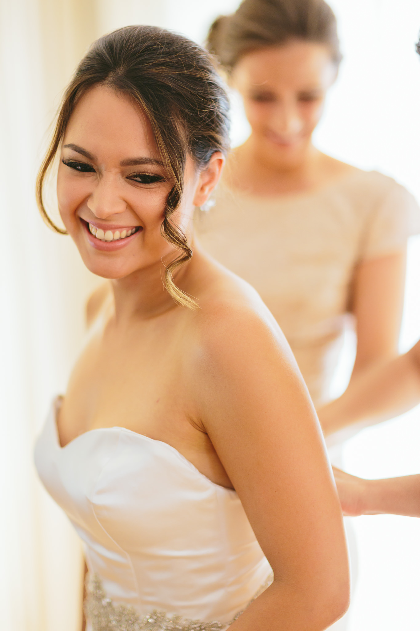 Bride getting zipped into dress