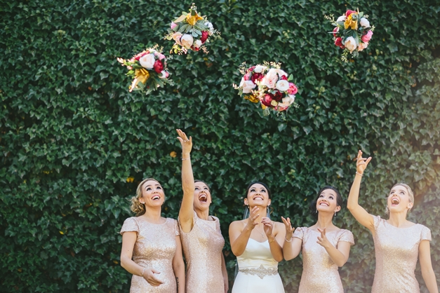 Bridesmaids throwing berry color bouquets