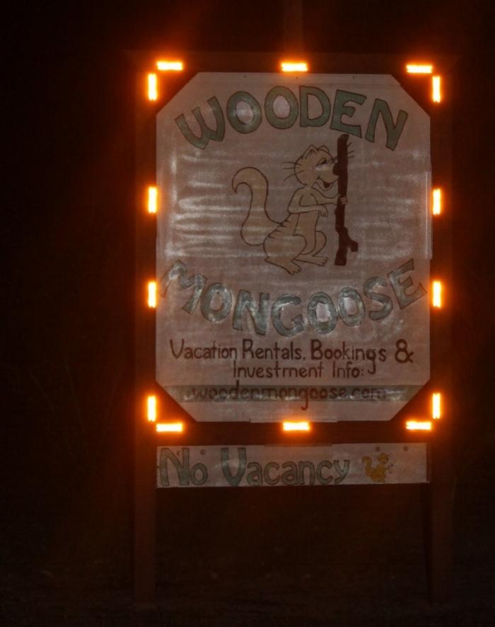 wooden mongoose sign at night.JPG